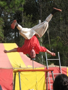 Performer at medieval fair stands on his head